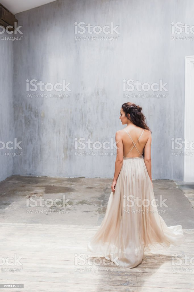 Bride with long black hair in studio, photo from back stock photo