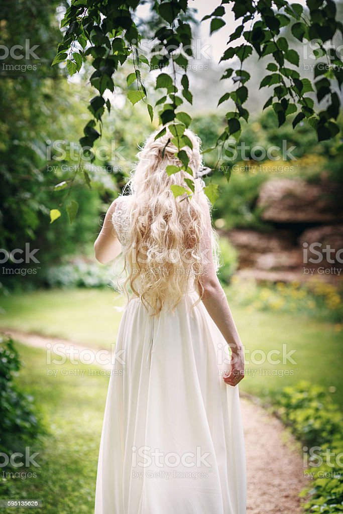 Bride with long fair hair from back in the garden stock photo