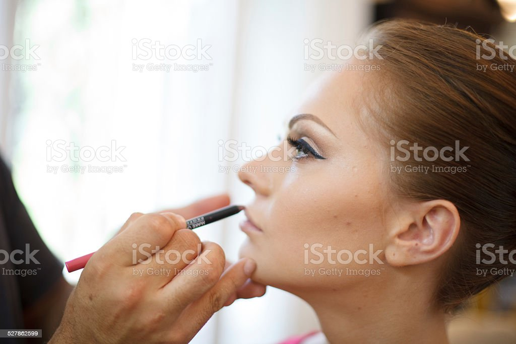 Bride with make-up artist stock photo