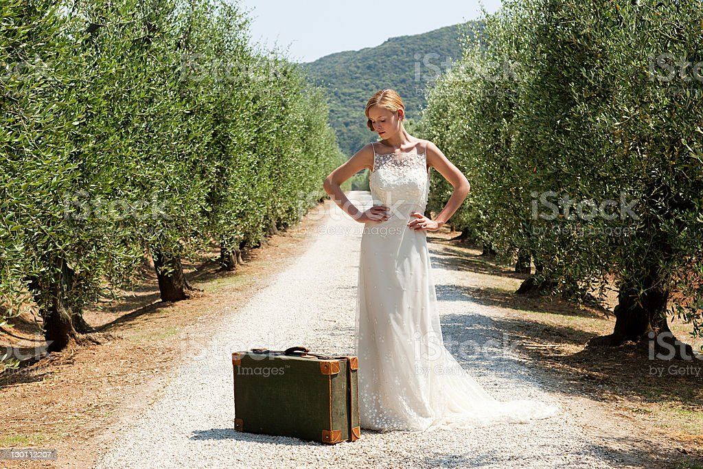 Bride with suitcase on country road, hands on hips stock photo