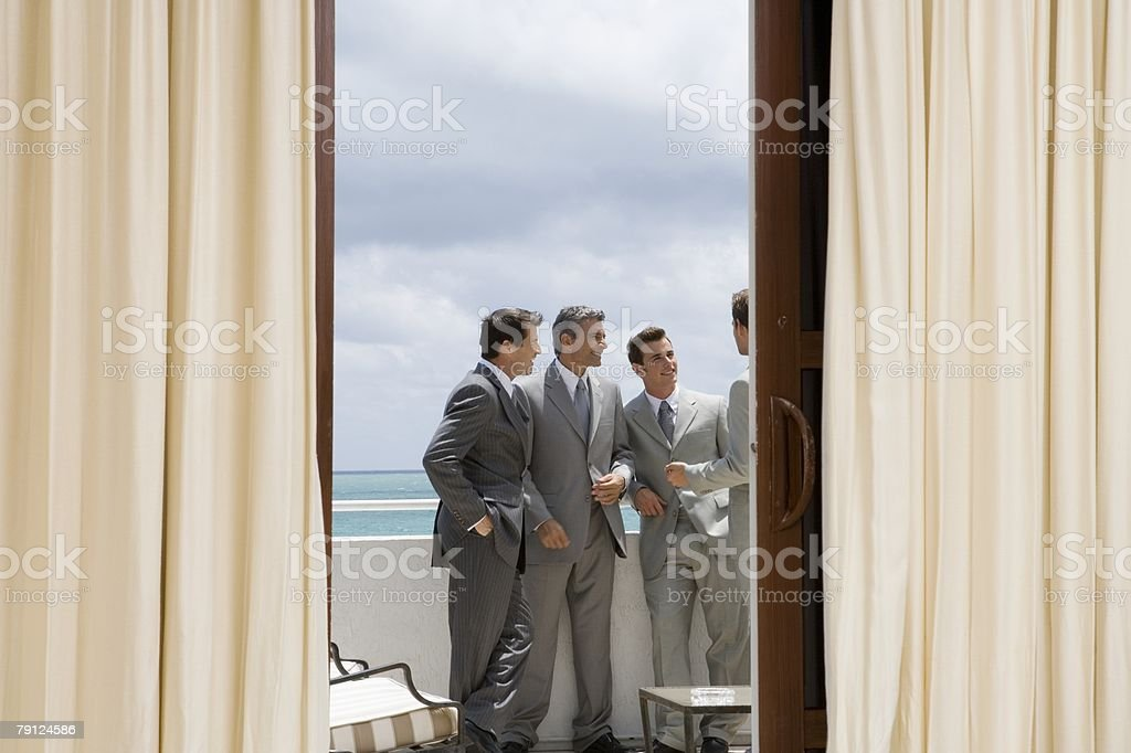 Bridegroom bestman and ushers on a balcony 免版稅 stock photo