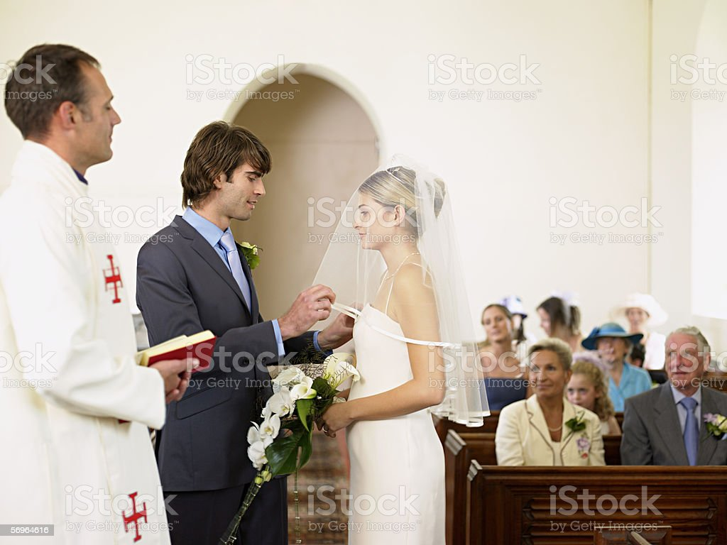 Bridegroom removing brides veil royalty-free stock photo
