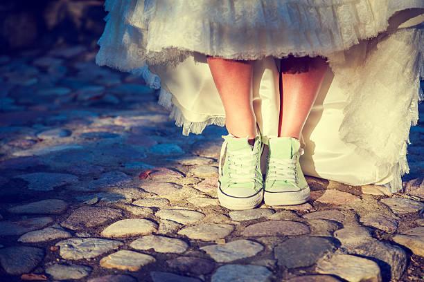 bride's feet in sneakers. hipster wedding concept. - hipster braut stock-fotos und bilder