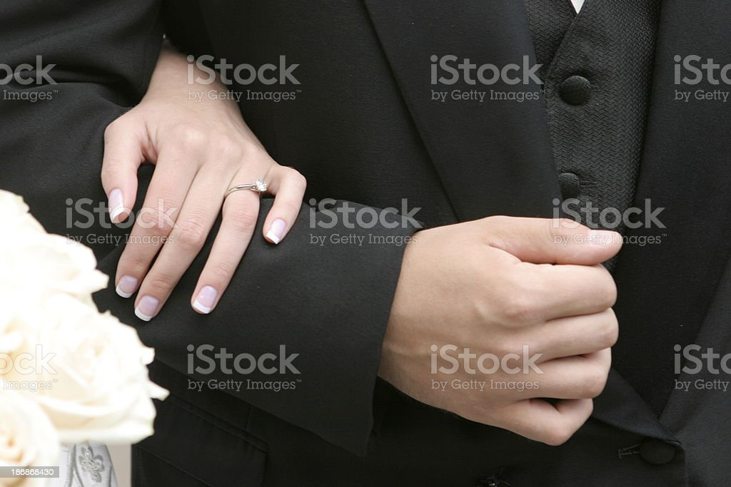 Bride's Hand Wearing Ring Holding Man's Arm stock photo