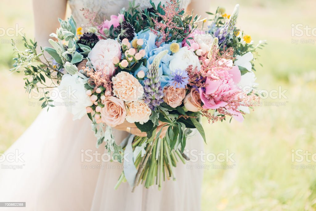 bride's hands hold beautiful bridal bouquet of peony. fine art photography. stock photo