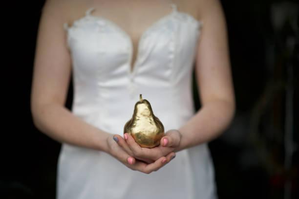 braut die hände halten eine goldenen birne-nahaufnahme - birnen verlobungsringe stock-fotos und bilder