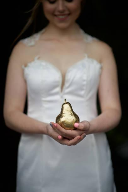 braut die hände halten eine goldene birne blickte - birnen verlobungsringe stock-fotos und bilder