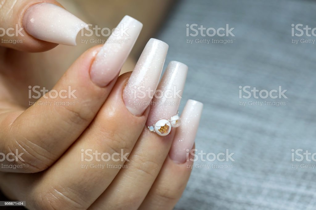 Close up of Bride\'s hands with simple manicure with a little jewel on...