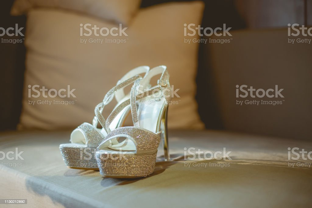 Bride's high heels shoes place on sofa in hotel room before wedding...