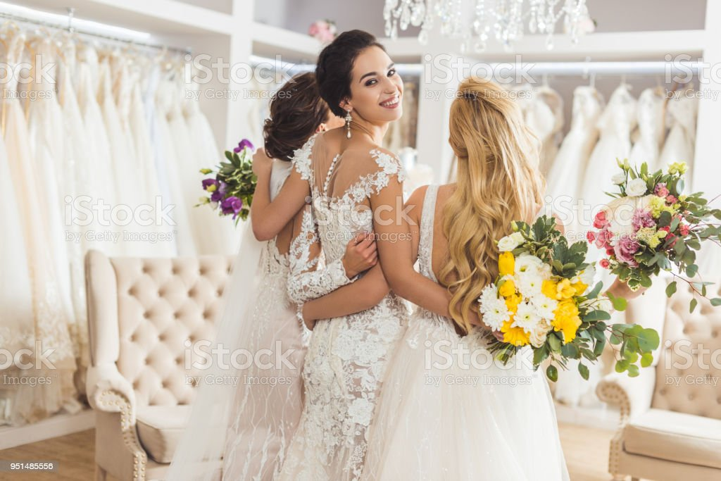 Brides in lace dresses with flowers in wedding atelier stock photo