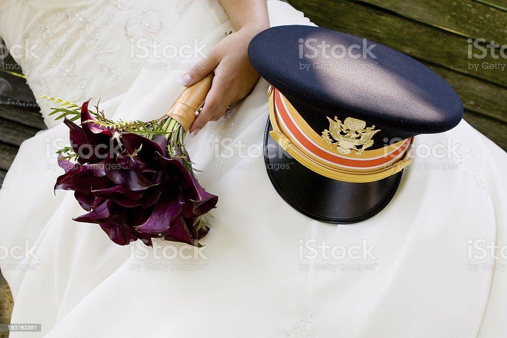 Bride's lap park bench with purple bouquet marine uniform hat stock photo
