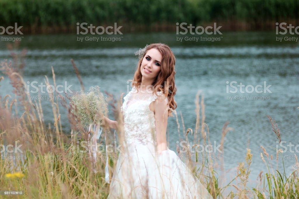 Gelinin portre beyaz düğün elbise ile buket yakın göl - Royalty-free Bahar Stok görsel