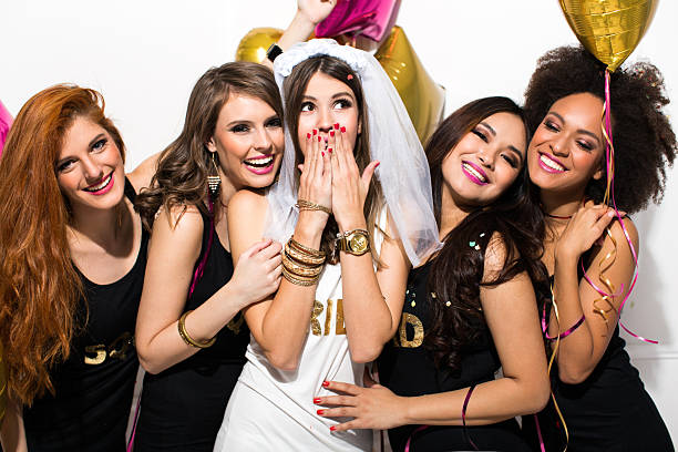 Bride's squad Young girlfriends celebrating bride night. Bride is wearing a veil and a T-shirt with the inscription ''BRIDE'', bridesmaids are wearing T-shirt with the inscription ''Squad''. They are laughing, dancing and singing.  Room is decorated with star and heart shaped balloons. bachelor stock pictures, royalty-free photos & images