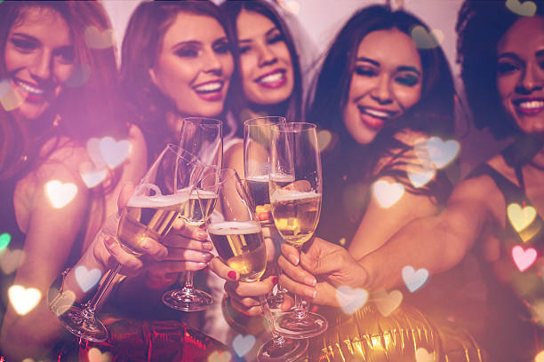 Bride's squad Young girlfriends celebrating bride night. Bride is wearing a veil and a T-shirt with the inscription ''BRIDE'', bridesmaids are wearing T-shirts with the inscription ''Squad''.  Standing in front of a white wall, cheering with champagne and dancing. Room is decorated with star and heart shaped balloons. bachelor stock pictures, royalty-free photos & images