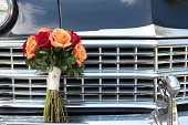 """""""Brides wedding bouquet of red and orange roses and gerbera daisies, sitting on the bumper of an antique,vintage car bumper in front of a chrome grill."""""""