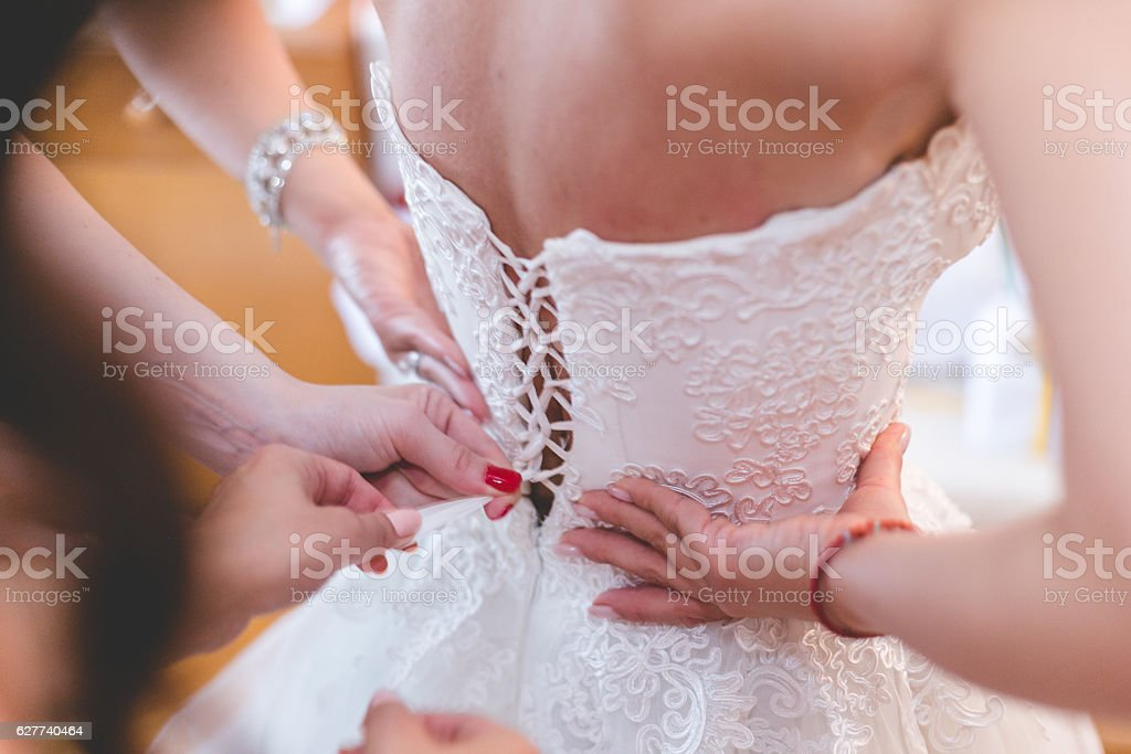 Bridesmaid dresses up the bride stock photo