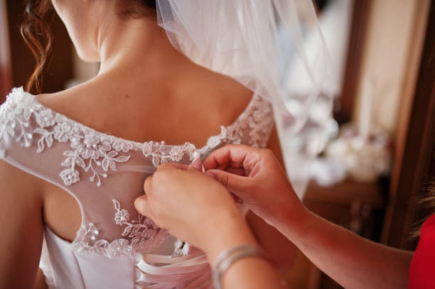 Bridesmaid helping to tie a ribbon on a wedding dress in a spacious room. stock photo