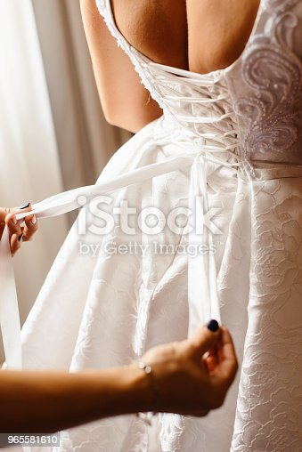 istock Bridesmaid makes bow knot on the back of brides wedding dress. Bridal morning of wedding day 965581610