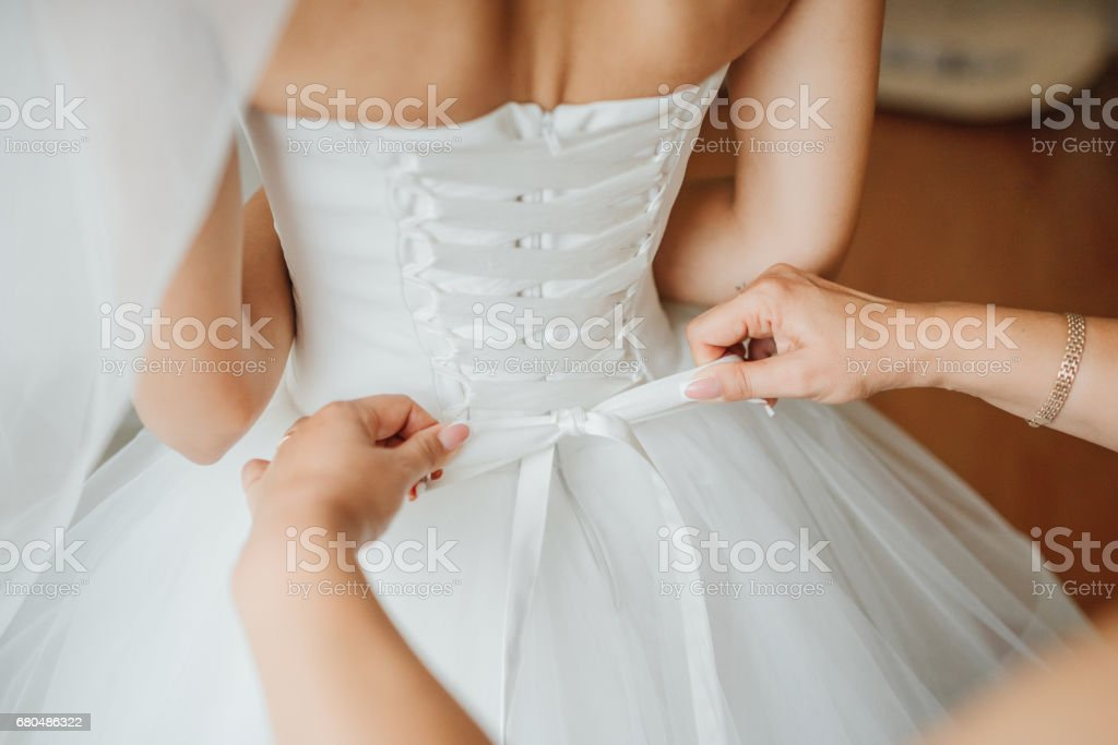 Bridesmaid makes bow-knot on the back of brides wedding dress stock photo