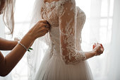 istock Bridesmaid making bow-knot on the back of brides wedding dress 942669646