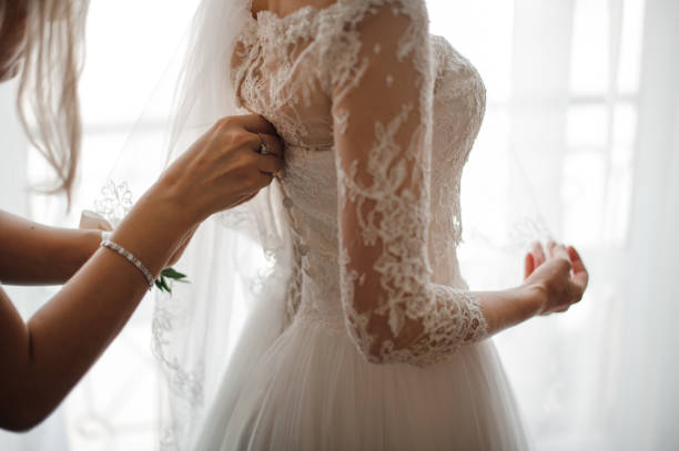 Bridesmaid making bow-knot on the back of brides wedding dress Bridesmaid making a bow-knot on the back of brides lacy white and beautiful wedding dress corset stock pictures, royalty-free photos & images