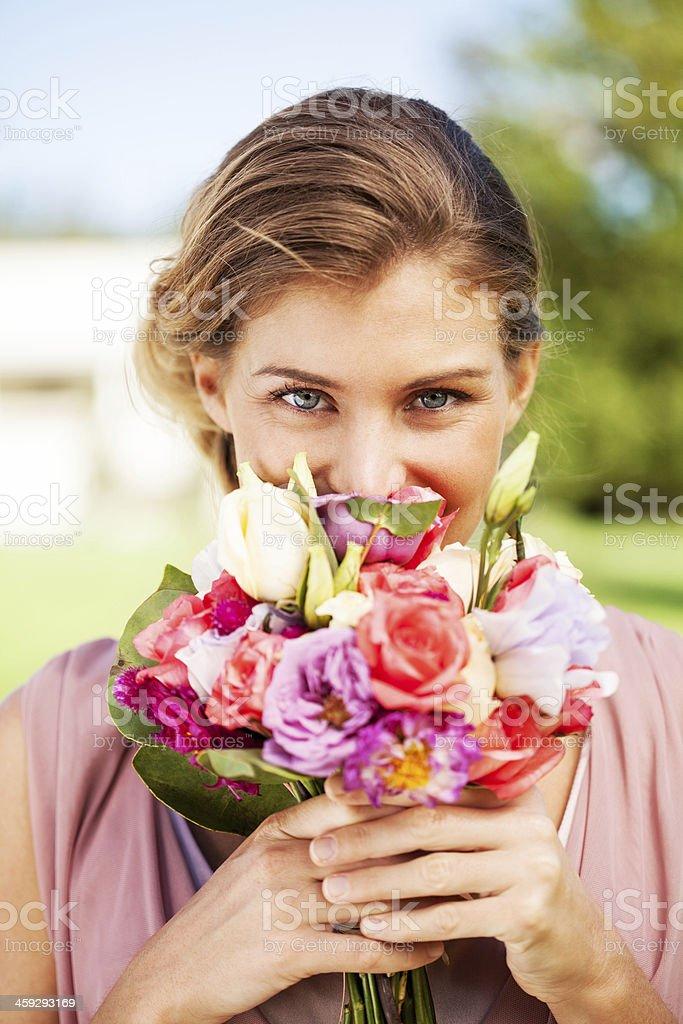 Подружка невесты Выглядывать на Букет из роз в саду стоковое фото