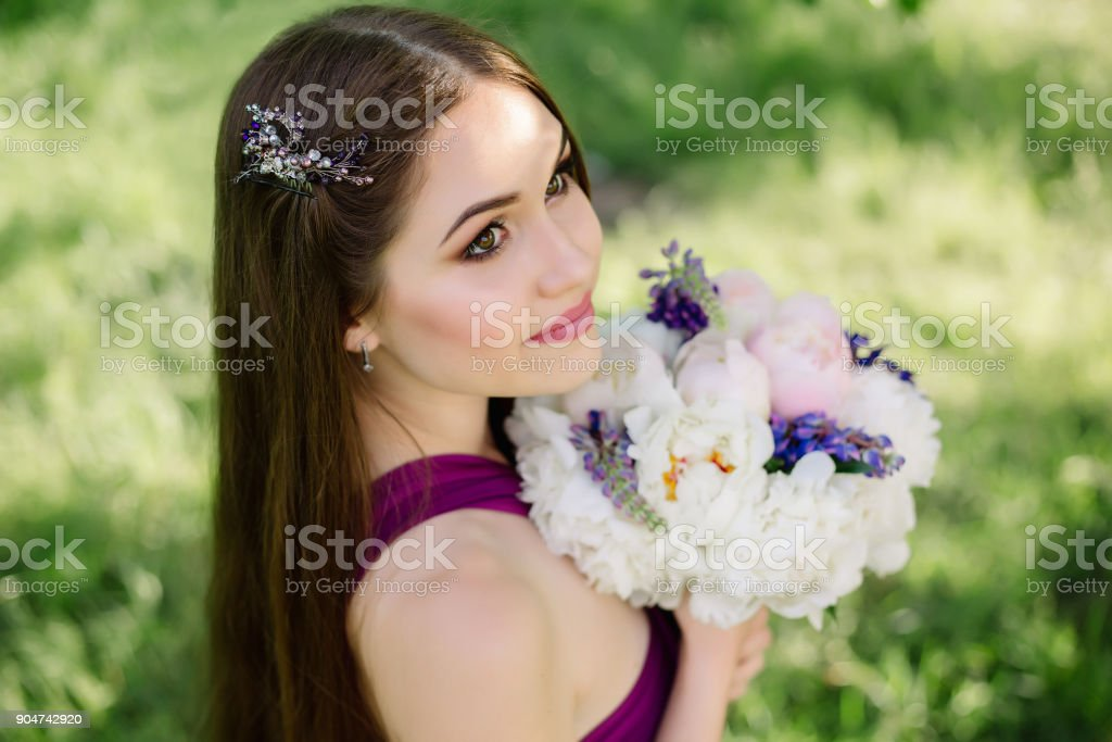 Bridesmaid with luxurious colorful wedding bouquet of peonies and other flowers standing at the ceremony in purple violet dress smiling and looking up hair vine wreath crystal rhinestones crown stock photo