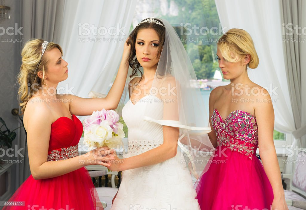 Bridesmaides elping a nervous bride to get ready stock photo