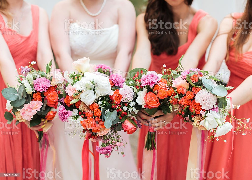 Bridesmaids and bride holds bouquets in hand. stock photo