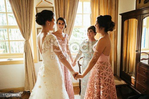 Bridesmaids and bride praying before wedding ceremony