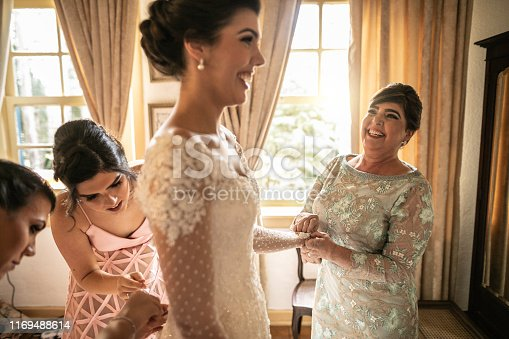 Bridesmaids helping bride getting dressed for the wedding ceremony