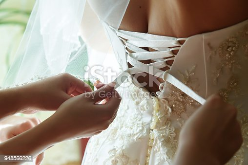 istock bridesmaids helping getting dressed bride in her luxury rich dress in the morning 948566226