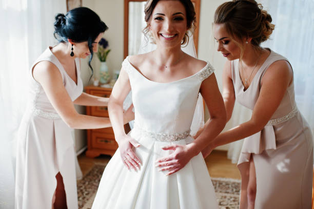 Bridesmaids helping gorgeous bride to dress up and get ready for her wedding ceremony. stock photo
