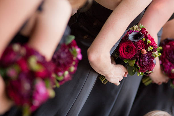 Bridesmaids in gray dresses with fuschia colored bouquets stock photo