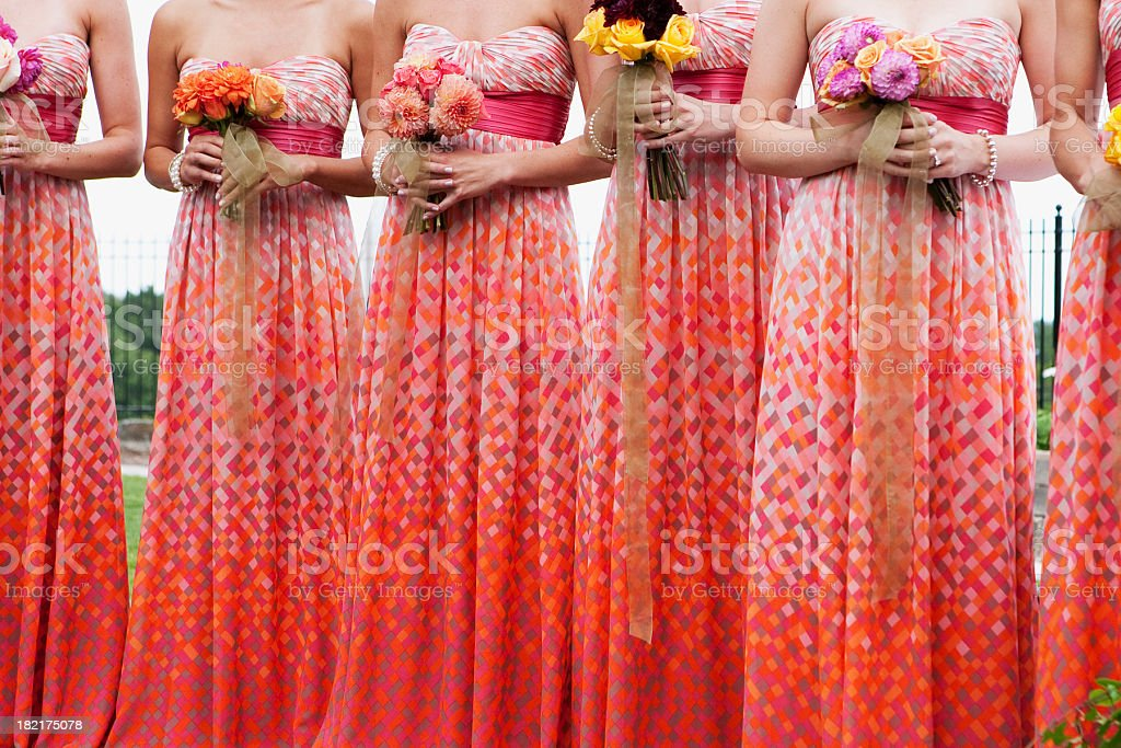 Bridesmaids wearing matching red patterned dresses stock photo