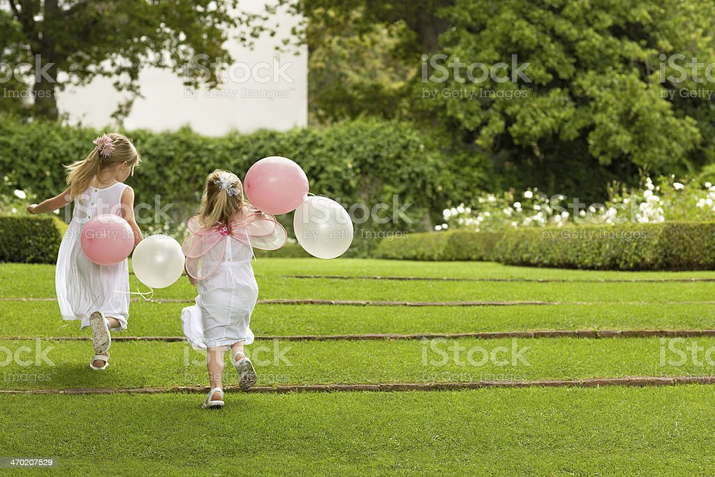 Bridesmaids With Balloons Running In Garden stock photo
