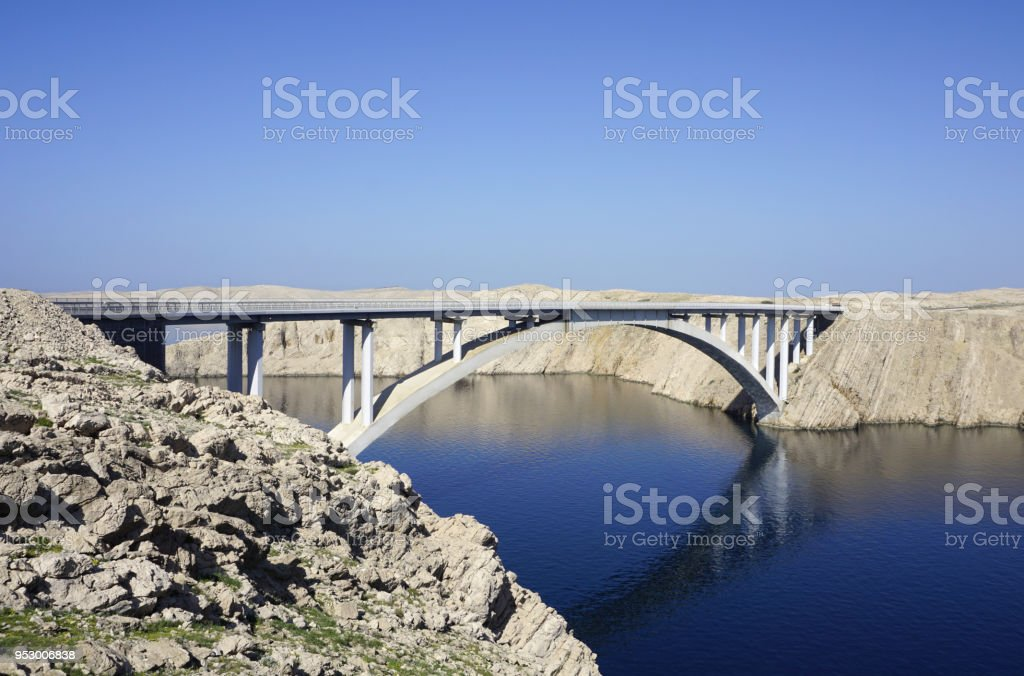 Bridge above the blue sea surface with reflection in the water, between the rocky land stock photo