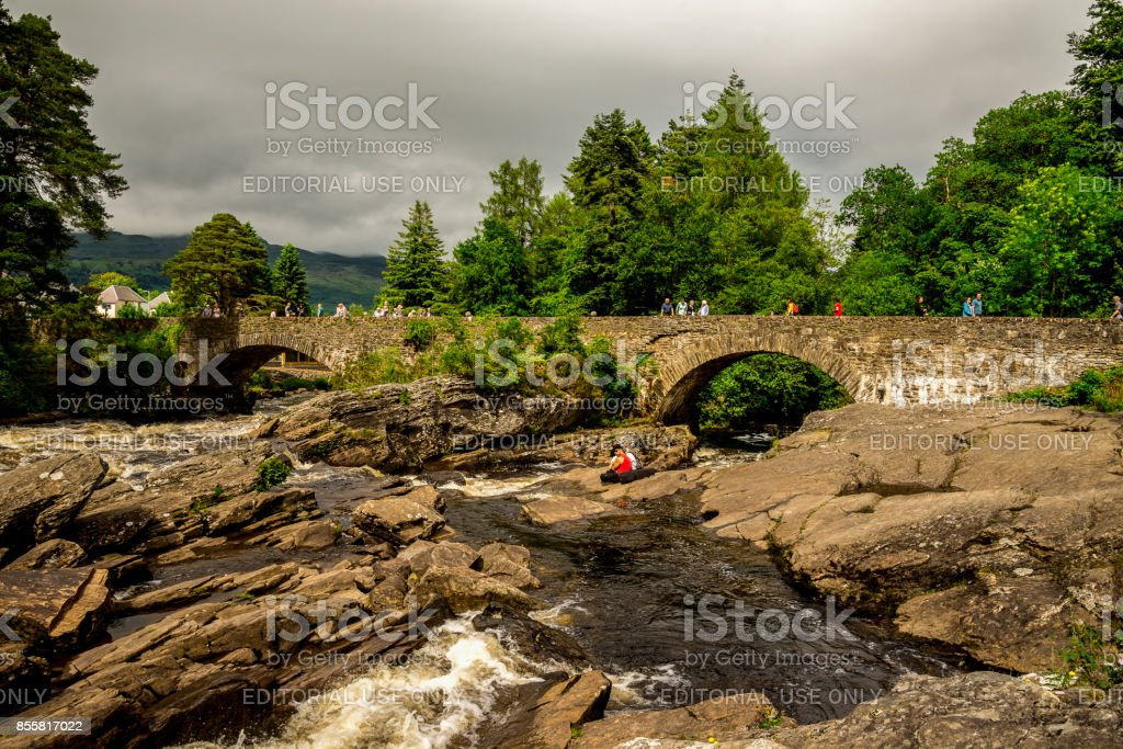 A bridge across falls of Dochart with tourists enjoying the view in a town of Killin, central Scotland stock photo
