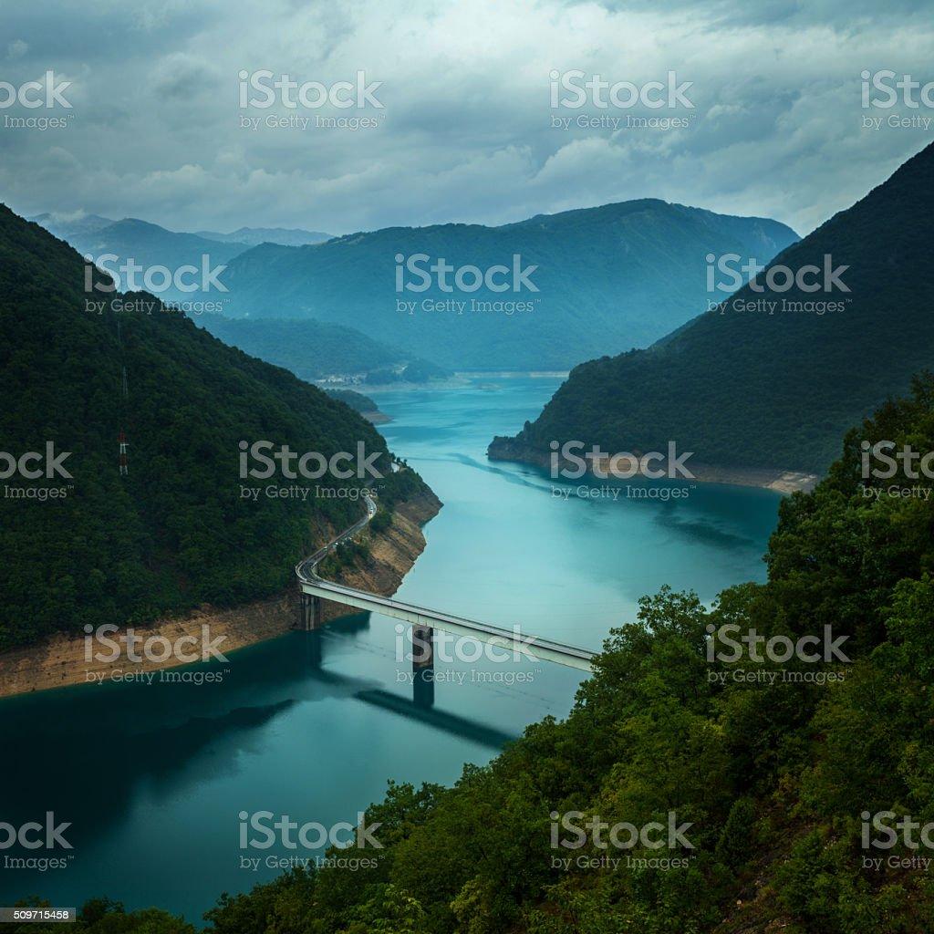 Bridge across the beautiful Pivska lake and mountains of Durmitor stock photo