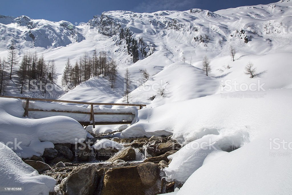 Bridge and flowing stream amid snow covered mountains. royalty-free stock photo