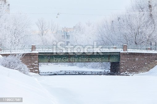 Heavy snowfall and old Baroque bridge over the river with wintering ducks.
