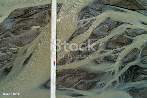 Aerial view of a small red car on the bridge and sand patterns on the river, South Coast Iceland