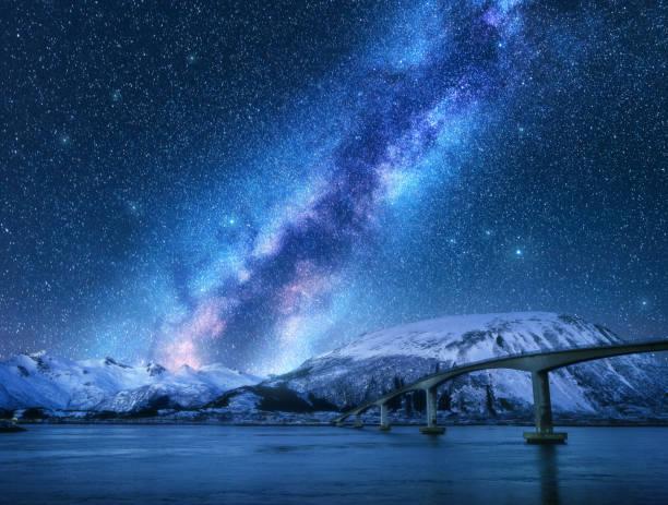 Brücke und Sternenhimmel mit Milchstraße über schneebedeckten Bergen, die sich im Wasser spiegeln. Nachtlandschaft mit Straße, verschneiten Felsen, Himmel mit Sternen und helle Milchstraße, Meer. Winter in Lofoten, Norwegen – Foto