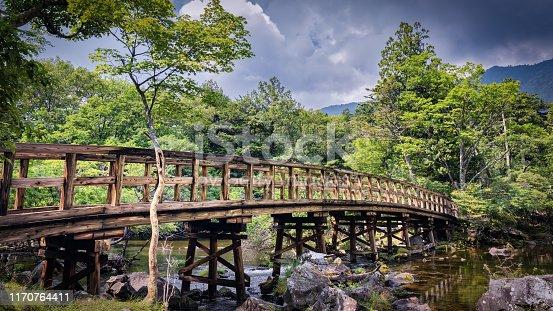 A bridge crossing the beginning of the Yu River and Yudaki Falls from Yuno Lake near Nikko, Japan