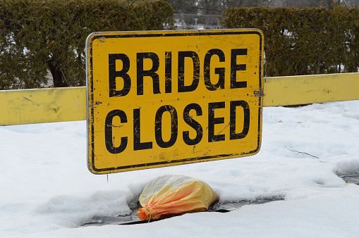 A sign informing traffic that the local bridge is currently closed for safety reasons.