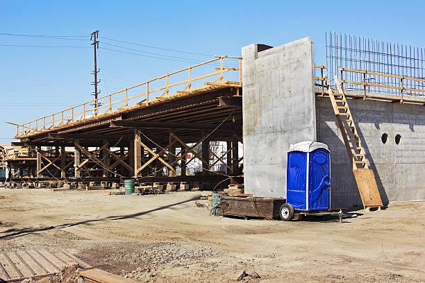 Bridge Construction with Porta Potty Bridge construction begins to go over a road and while a porta potty is good to have on site. portable toilet stock pictures, royalty-free photos & images