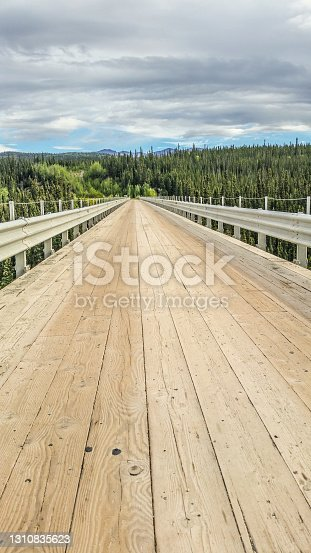 A wooden bridge fades into the distance in Interior Alaska. The Kuskalana Bridge is a great accomplishment in Interior Alaska, spanning across a deep gorge.
