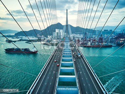 istock Bridge in Hong Kong and Container Cargo freight ship 1058737714