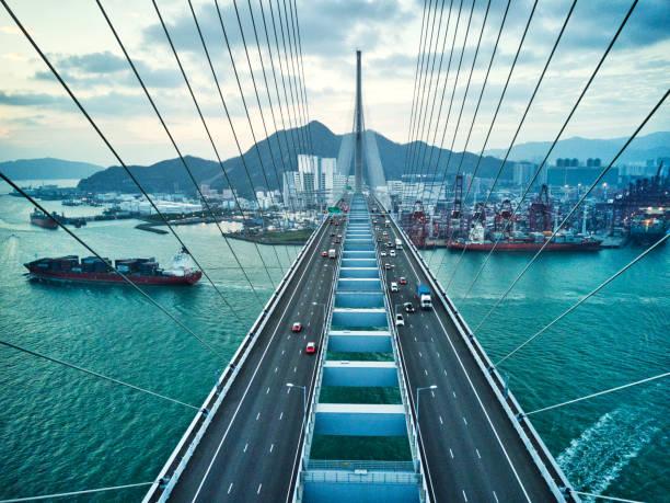 brücke in hong kong und containerladung frachtschiff - internationale geschäftswelt stock-fotos und bilder