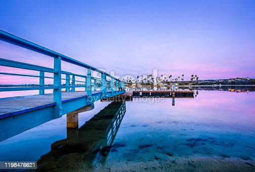 Wide-angle view of bridge leading to a dock on Mission Bay in San Diego, California at dawn